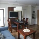 """Apartament """"Dziewiąta Fala"""" – salon z widokiem na aneks kuchenny i wyjście na taras"""